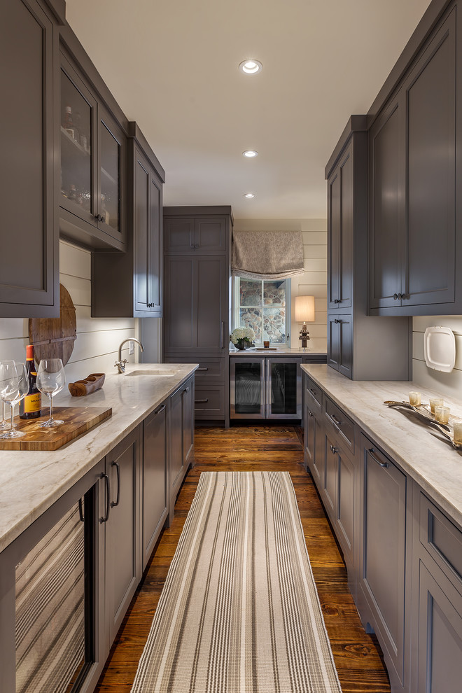 Wet bar - large country galley brown floor and dark wood floor wet bar idea in Other with an undermount sink, gray cabinets, shaker cabinets, marble countertops, white backsplash, wood backsplash and gray countertops