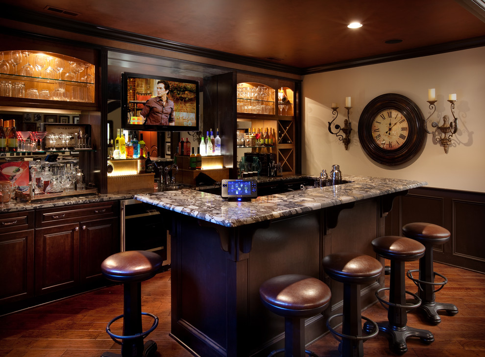 Inspiration for a timeless galley dark wood floor and brown floor seated home bar remodel in Columbus with raised-panel cabinets, dark wood cabinets and multicolored countertops