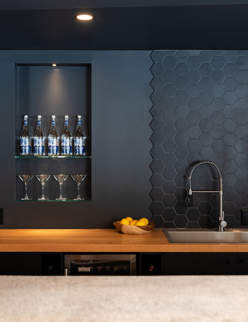 Photo of a contemporary single-wall wet bar in Toronto with a drop-in sink, flat-panel cabinets, black cabinets, wood benchtops, black splashback and brown benchtop.