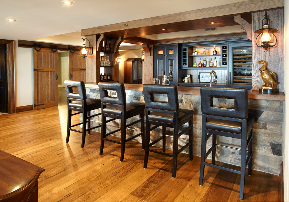 Inspiration for a mid-sized rustic galley medium tone wood floor and brown floor seated home bar remodel in Toronto with wood countertops, glass-front cabinets, distressed cabinets and brown countertops