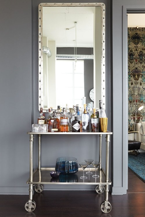 Hang an oversized mirror above a bar cart to create a focal point in a room. See all 15 CREATIVE ways to use and style a bar cart in your home.