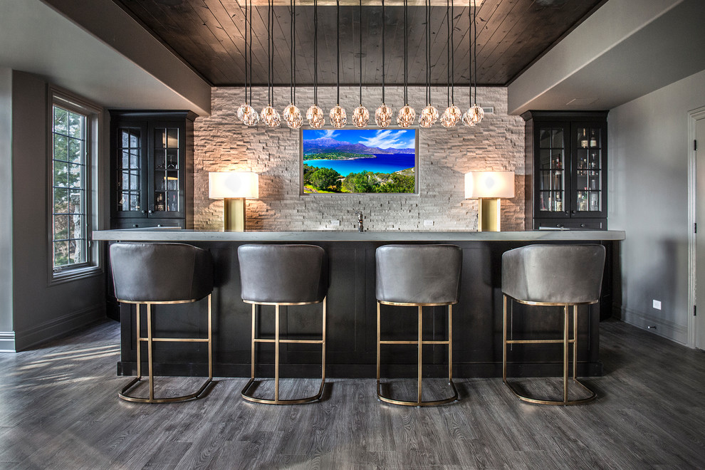 Minimalist galley dark wood floor and gray floor seated home bar photo in Chicago with glass-front cabinets, black cabinets, concrete countertops, gray backsplash, stone tile backsplash and gray countertops