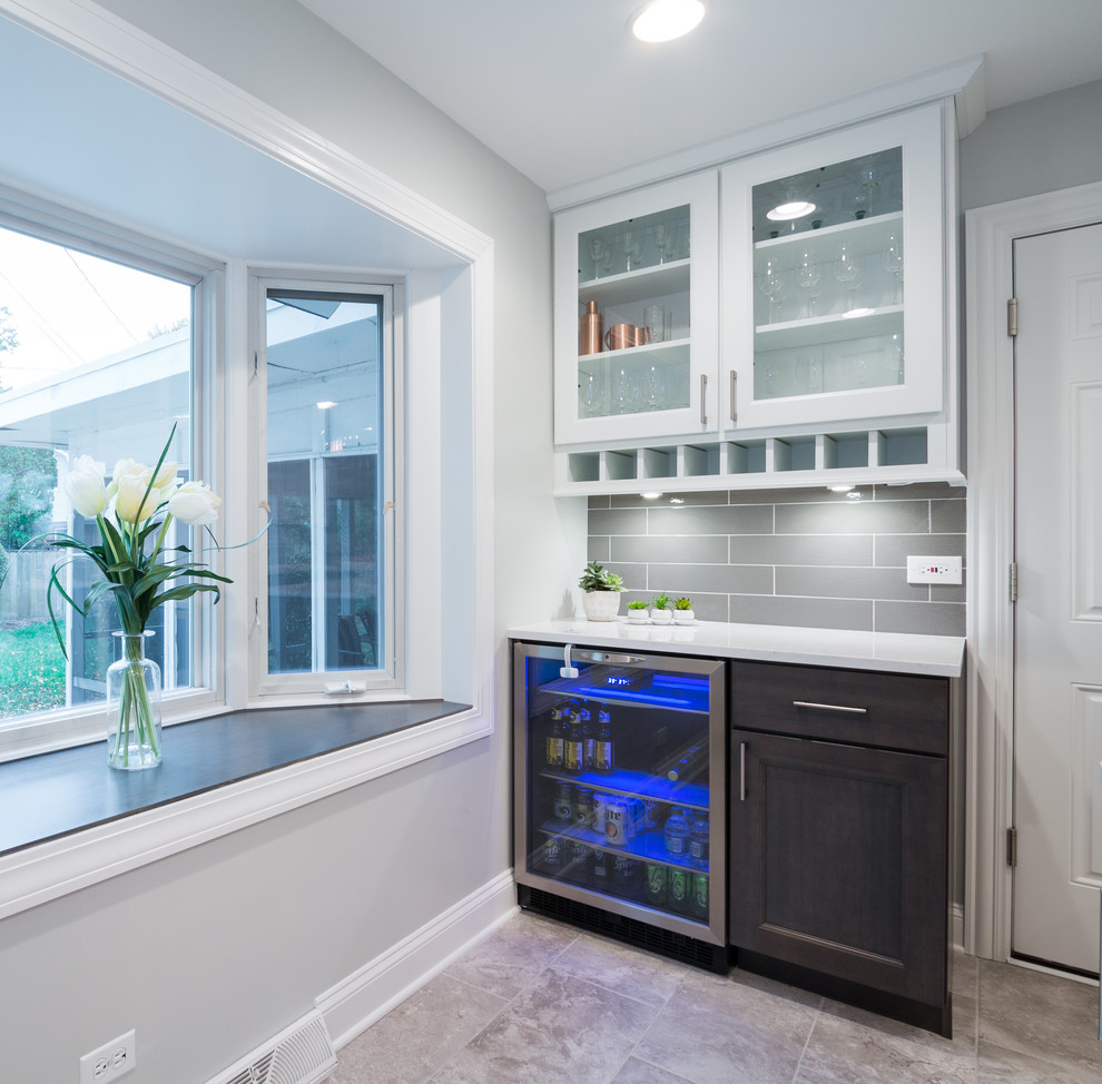 Small transitional single-wall porcelain tile and beige floor wet bar photo in Chicago with white cabinets, quartz countertops, gray backsplash, porcelain backsplash, glass-front cabinets and white countertops