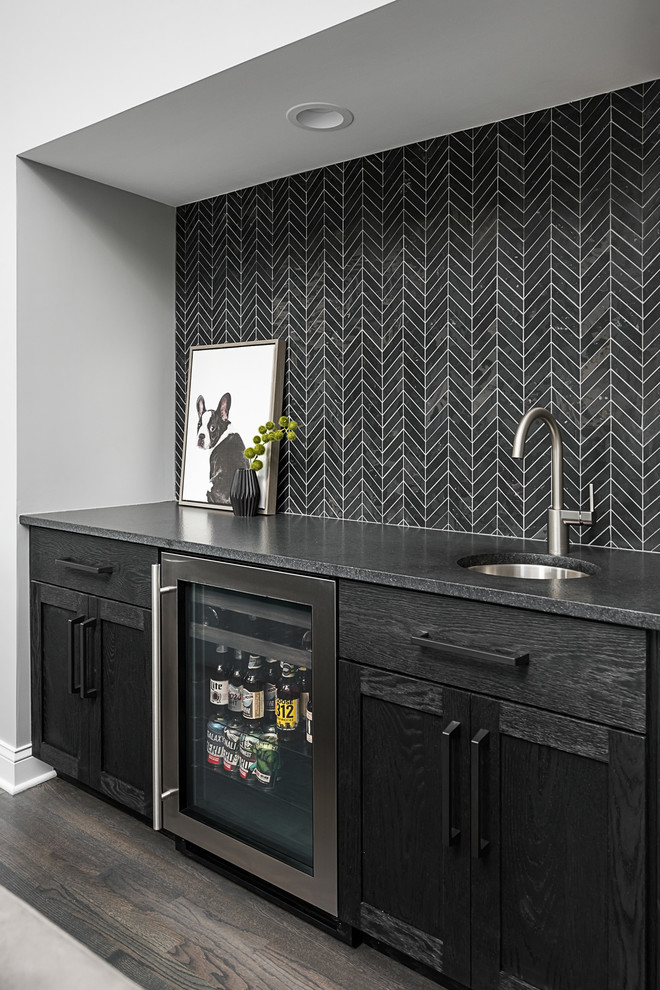 Inspiration for a mid-sized transitional single-wall dark wood floor and brown floor wet bar remodel in Chicago with an undermount sink, black cabinets, black backsplash, black countertops, shaker cabinets and soapstone countertops