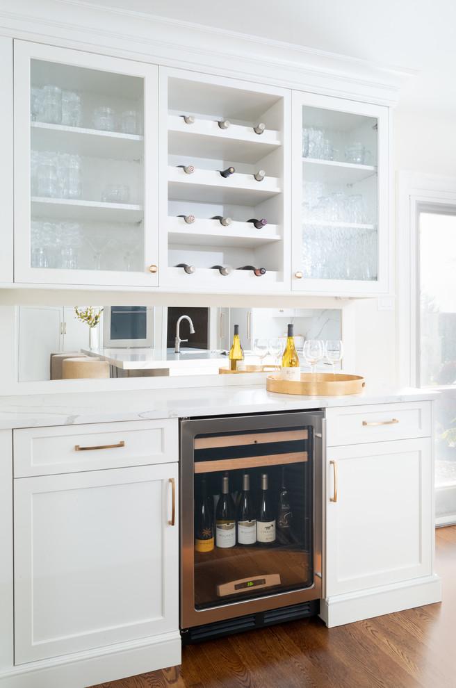 Home bar - transitional single-wall medium tone wood floor home bar idea in Philadelphia with shaker cabinets, white cabinets, quartz countertops, no sink, mirror backsplash and white countertops