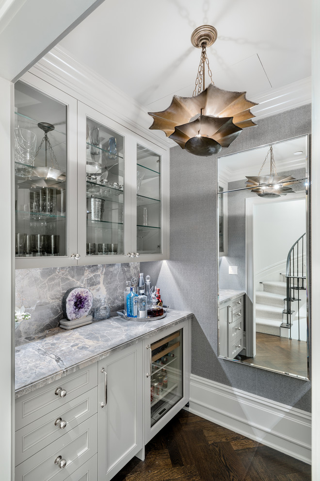 Home bar - small transitional single-wall dark wood floor and brown floor home bar idea in New York with glass-front cabinets, white cabinets and gray backsplash