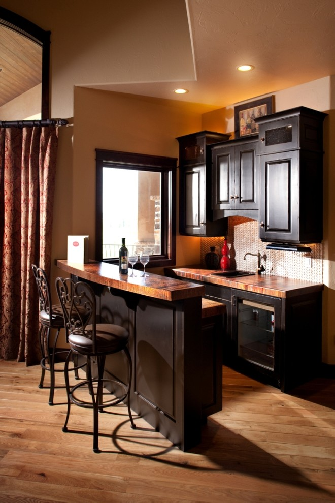 Mid-sized elegant galley medium tone wood floor seated home bar photo in Denver with a drop-in sink, raised-panel cabinets, dark wood cabinets, wood countertops and brown countertops