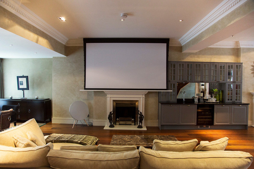 Home theater - large traditional open concept dark wood floor home theater idea in London with gray walls and a wall-mounted tv