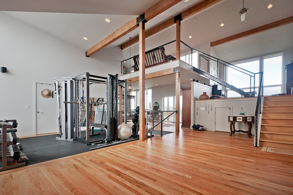 Inspiration for a large contemporary medium tone wood floor home weight room remodel in Seattle with white walls