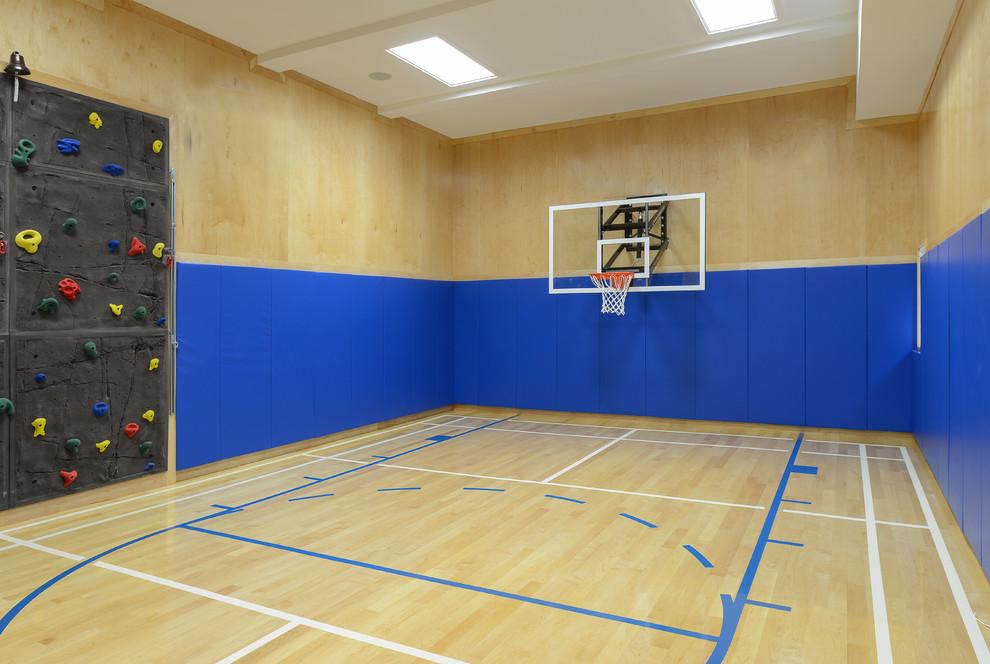 Geräumiger Moderner Fitnessraum mit Indoor-Sportplatz, blauer Wandfarbe und hellem Holzboden in New York