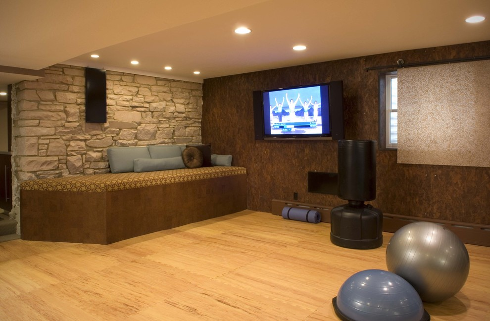 Example of a trendy light wood floor and orange floor home gym design in Denver with brown walls