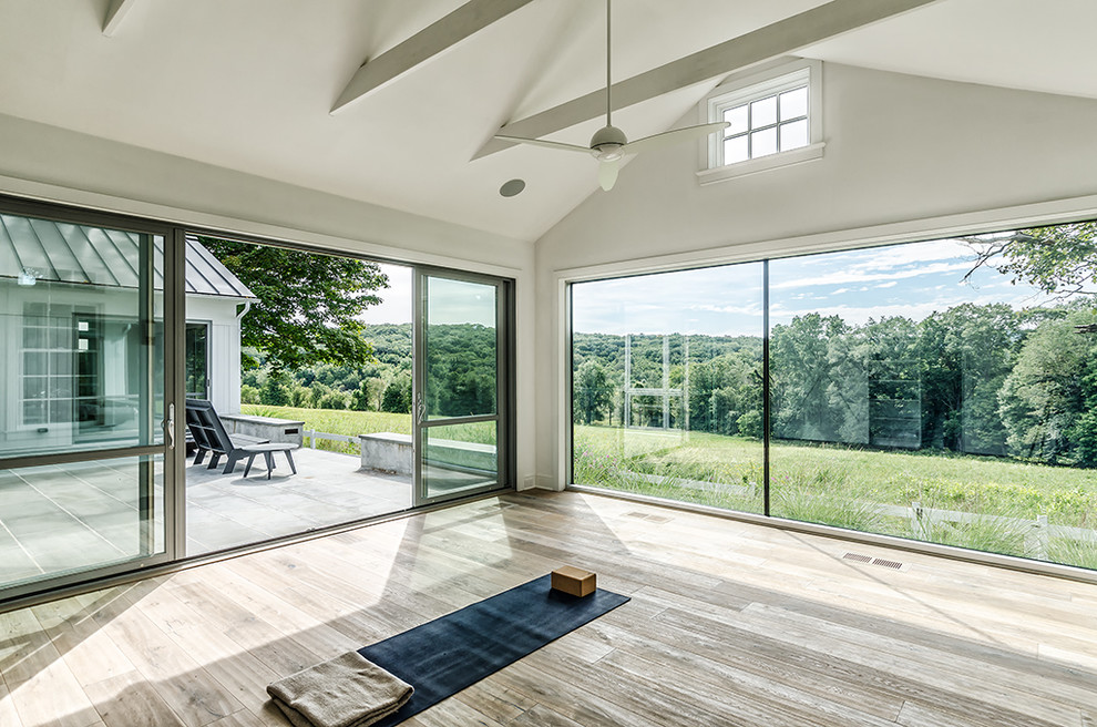 Mid-sized country light wood floor home yoga studio photo in New York with white walls