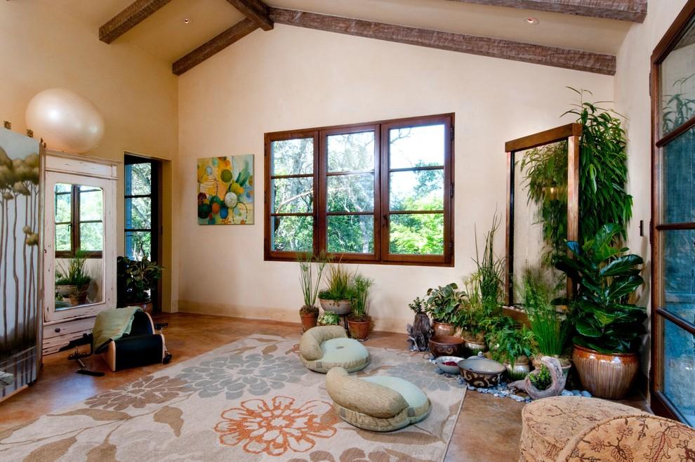 Home yoga studio - large mediterranean travertine floor and brown floor home yoga studio idea in San Francisco with beige walls
