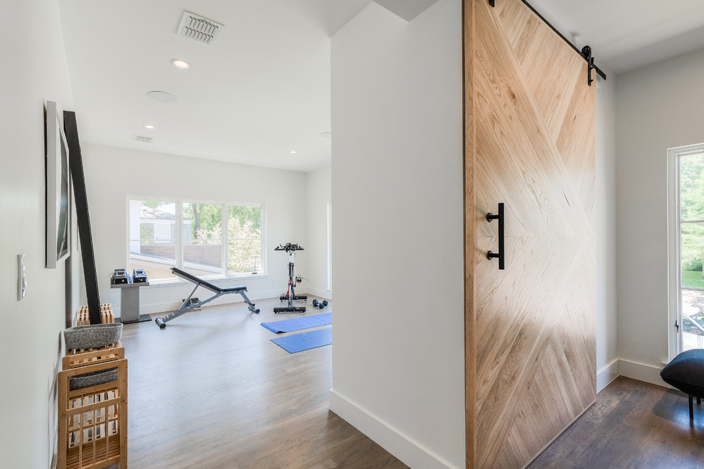 Example of a large trendy light wood floor home yoga studio design in Dallas with white walls
