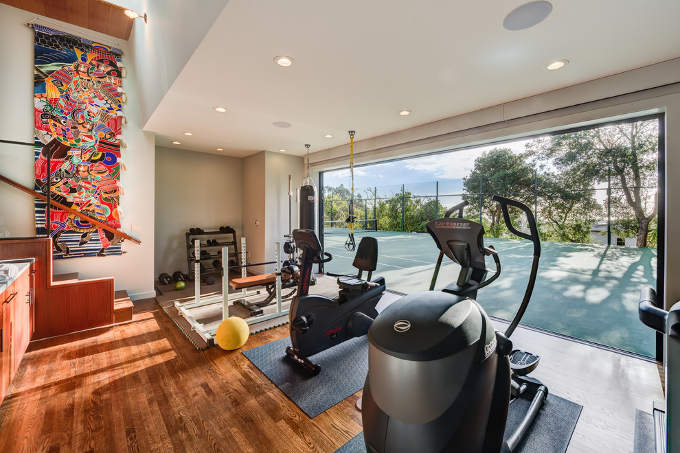Inspiration for a mid-sized contemporary medium tone wood floor and brown floor multiuse home gym remodel in San Francisco with white walls