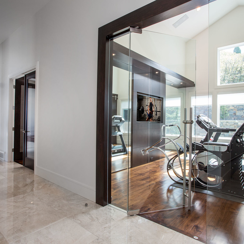 Example of a trendy medium tone wood floor multiuse home gym design in Salt Lake City with white walls