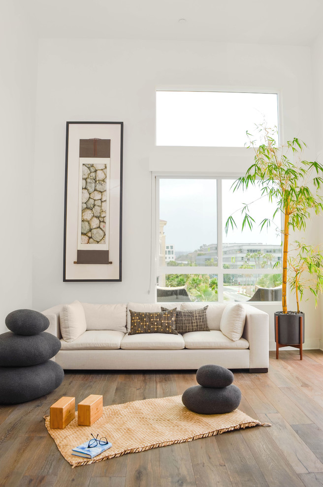 Example of a large trendy medium tone wood floor and gray floor home yoga studio design in Los Angeles with white walls