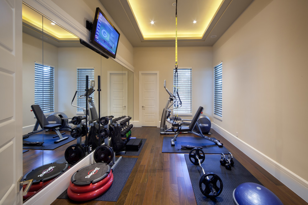 Inspiration for a timeless dark wood floor and brown floor home weight room remodel in Orlando with beige walls