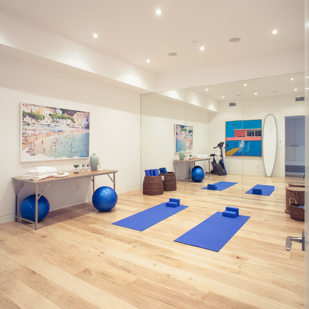 Large trendy medium tone wood floor multiuse home gym photo in Los Angeles with white walls