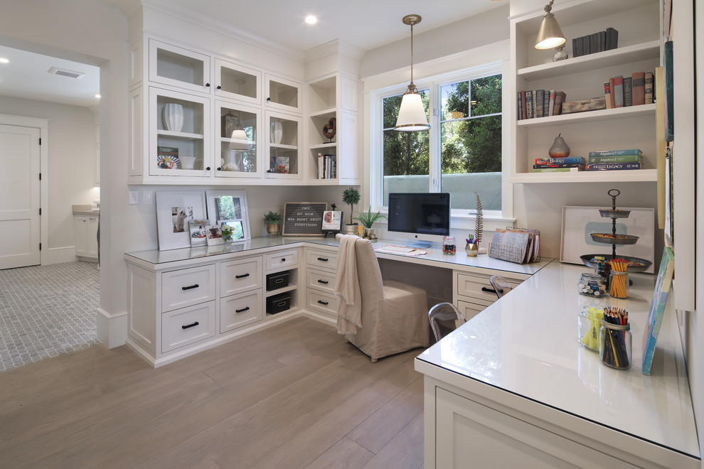 Example of a transitional built-in desk medium tone wood floor and brown floor study room design in Orange County with gray walls