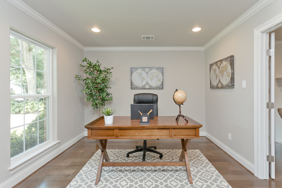 Elegant freestanding desk medium tone wood floor study room photo in Houston with gray walls