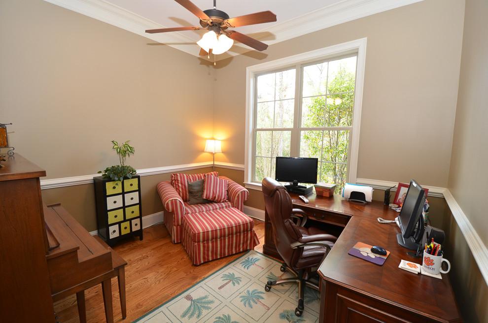 Elegant freestanding desk medium tone wood floor study room photo in Atlanta with beige walls