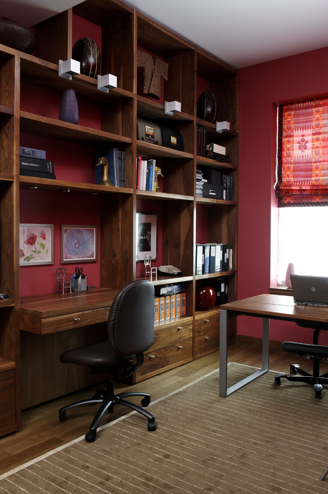 Home office - contemporary built-in desk home office idea in New York with red walls