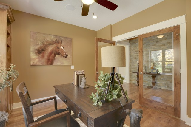 Example of a cottage freestanding desk medium tone wood floor and brown floor study room design in Minneapolis with brown walls