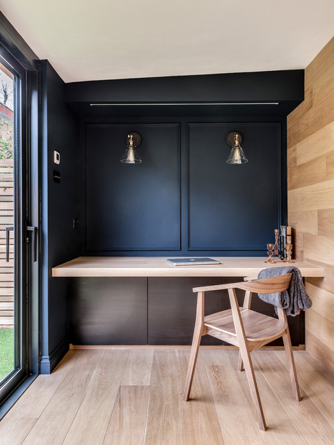 Inspiration for a scandinavian light wood floor and beige floor home office remodel in London with black walls