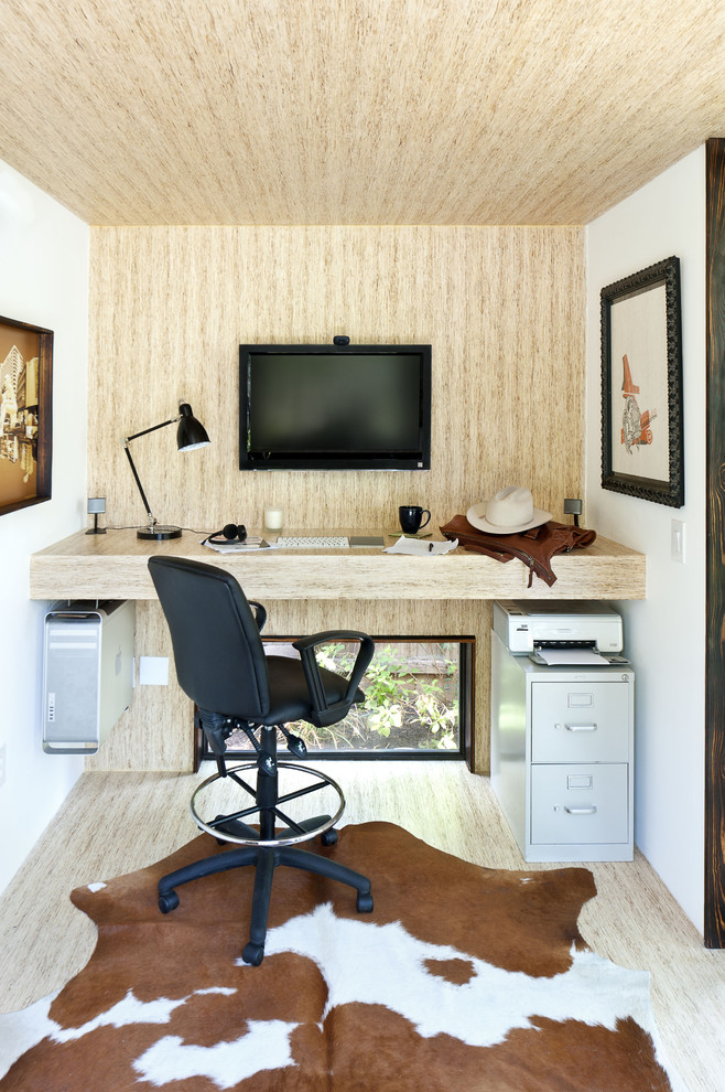Example of a mid-sized minimalist built-in desk home office design in Austin with beige walls