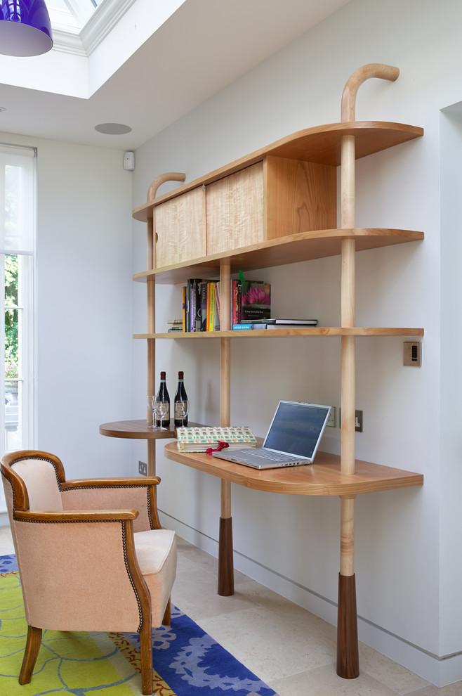 Trendy built-in desk beige floor study room photo in London with white walls