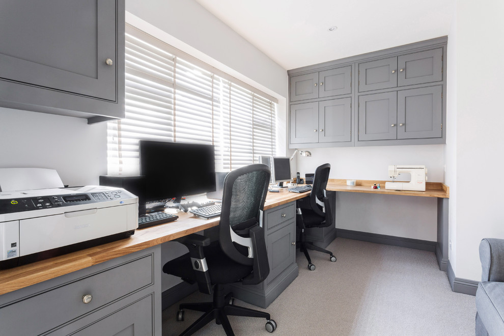 Inspiration for a mid-sized transitional built-in desk carpeted and gray floor study room remodel in Essex with white walls