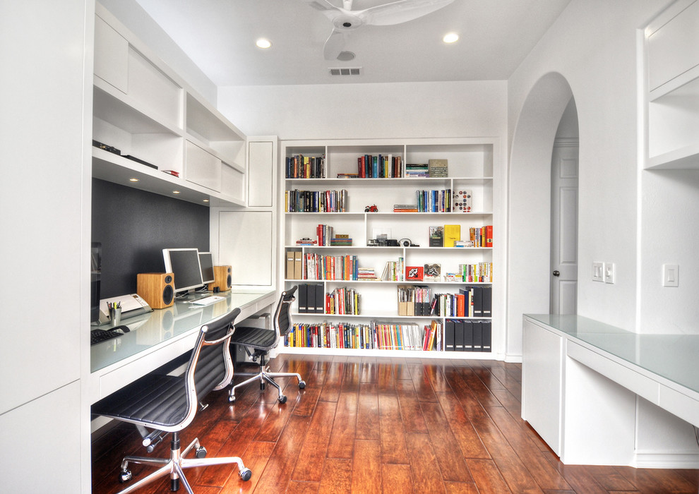 Example of a large trendy built-in desk medium tone wood floor home office design in Orange County with white walls and no fireplace