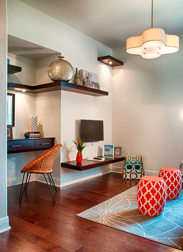 Example of a transitional built-in desk dark wood floor study room design in Miami with gray walls
