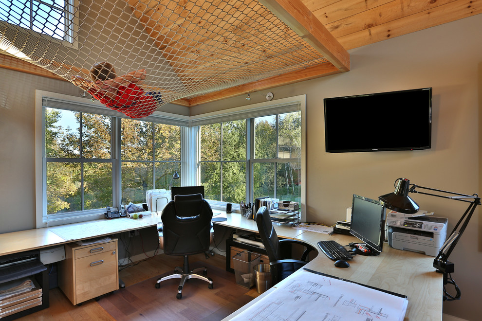 Example of a transitional built-in desk medium tone wood floor and brown floor home studio design in Portland Maine with beige walls