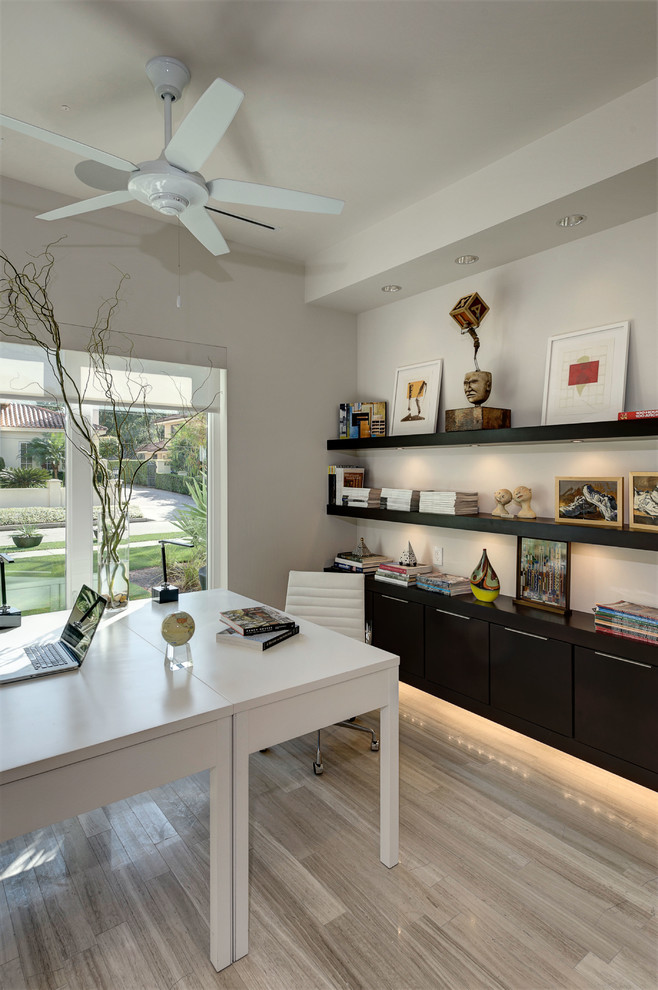 Home office - modern freestanding desk light wood floor home office idea in Orlando with white walls