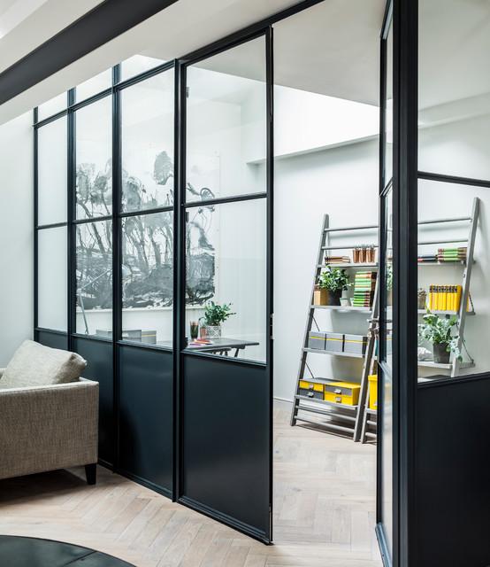 Esempio di uno studio minimal con pareti bianche e parquet chiaro