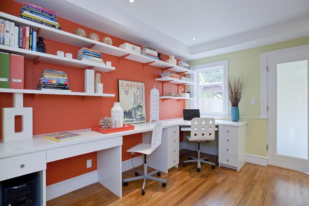 Home office - coastal built-in desk medium tone wood floor home office idea in San Francisco with orange walls