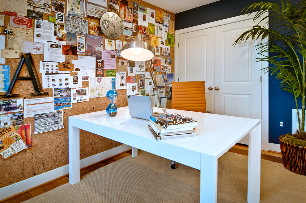 Example of a trendy freestanding desk medium tone wood floor home office design in DC Metro with blue walls