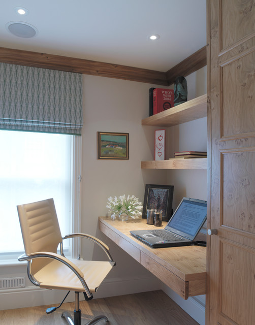 This is an example of a rural home office and library in London with a built-in desk.