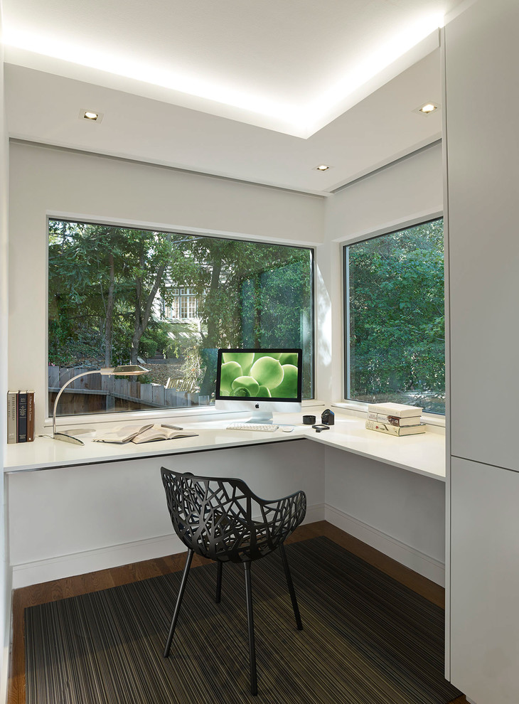 Example of a mid-sized minimalist built-in desk carpeted study room design in San Francisco with white walls