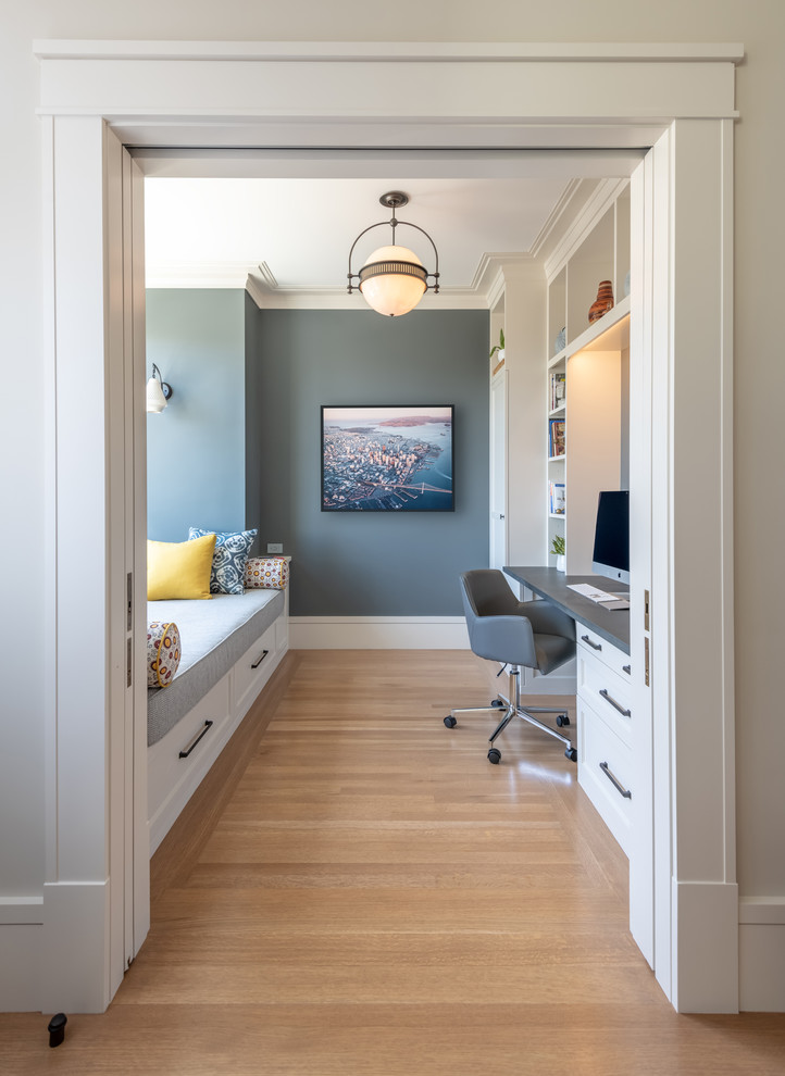 Study room - transitional built-in desk medium tone wood floor and brown floor study room idea in San Francisco with gray walls