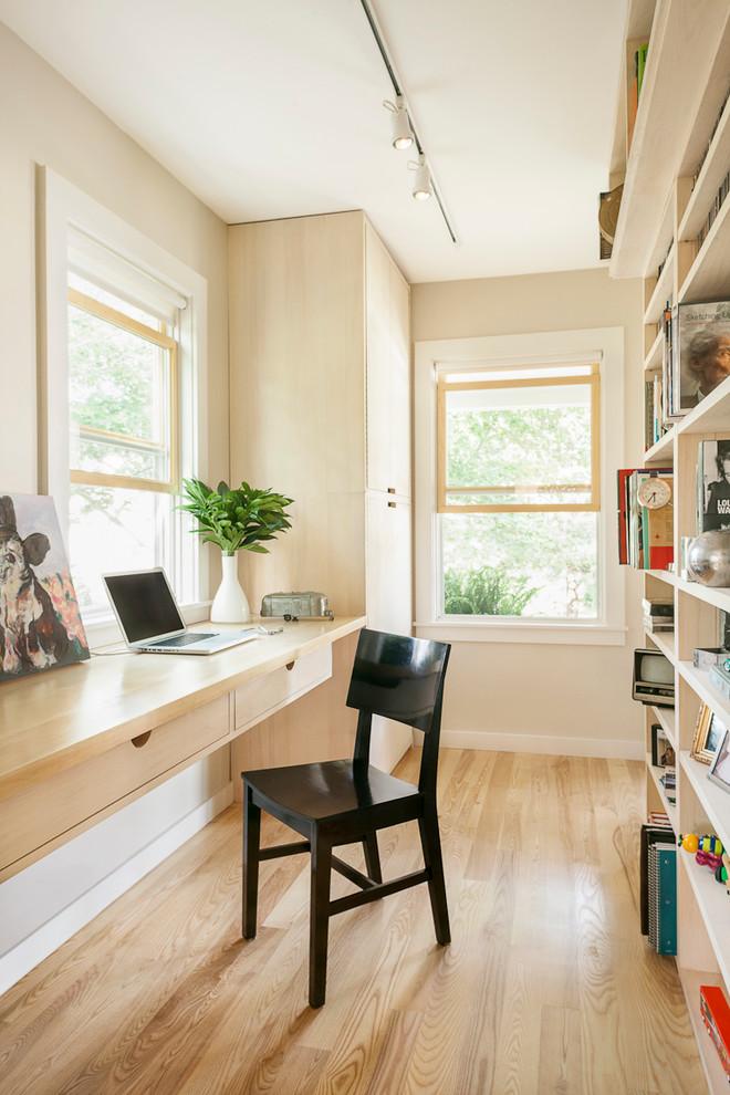 Esempio di uno studio minimal con scrivania incassata e pavimento beige