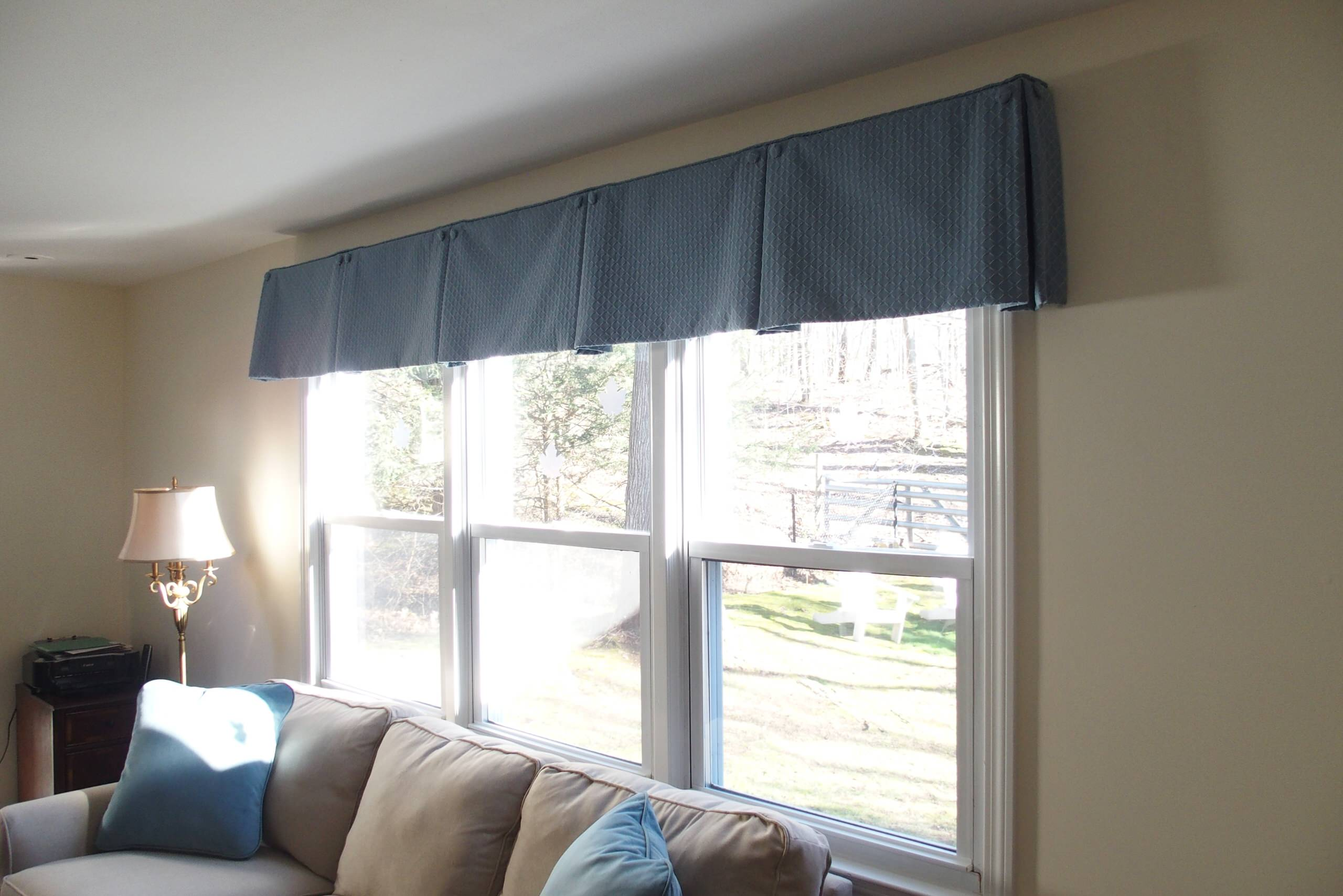 Box pleat valances enhanced with covered buttons in a quiet study