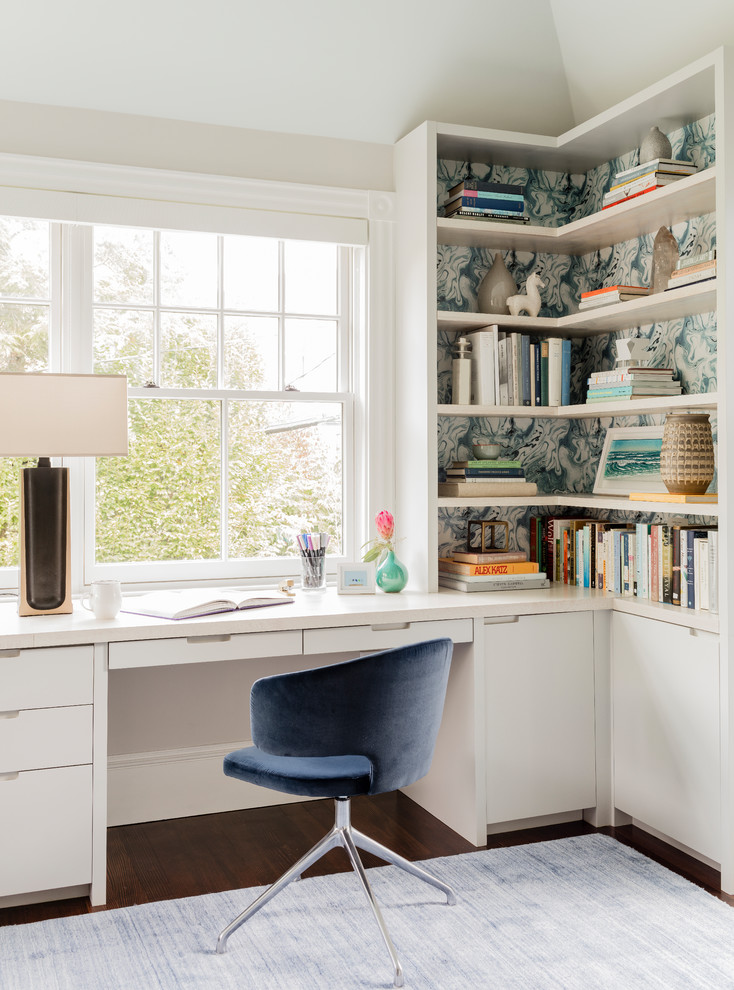 Mid-sized transitional built-in desk dark wood floor home office library photo in Boston with white walls