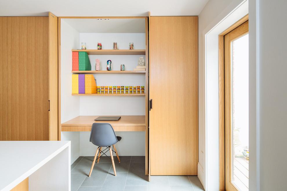 Réalisation d'un bureau design avec un mur blanc, un bureau intégré et un sol gris.