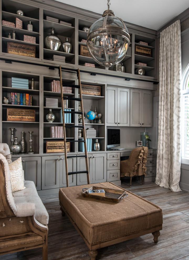 Elegant built-in desk dark wood floor home office library photo in Detroit with gray walls
