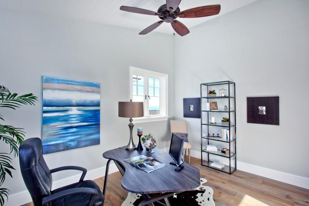 beach style home office with custom blue desk