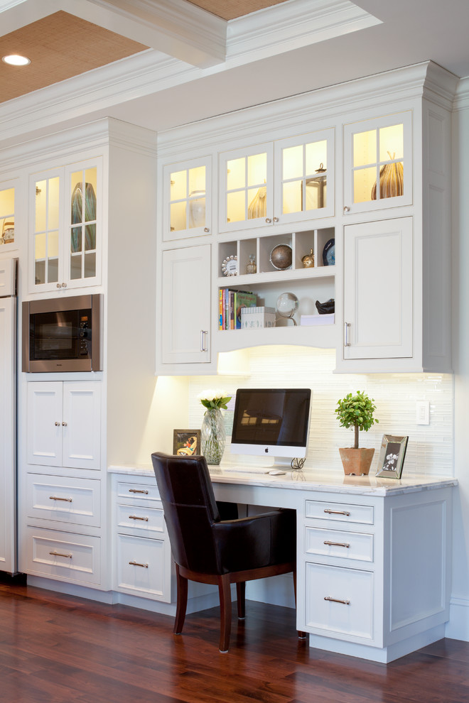 Home office - traditional built-in desk dark wood floor and coffered ceiling home office idea in Boston with white walls
