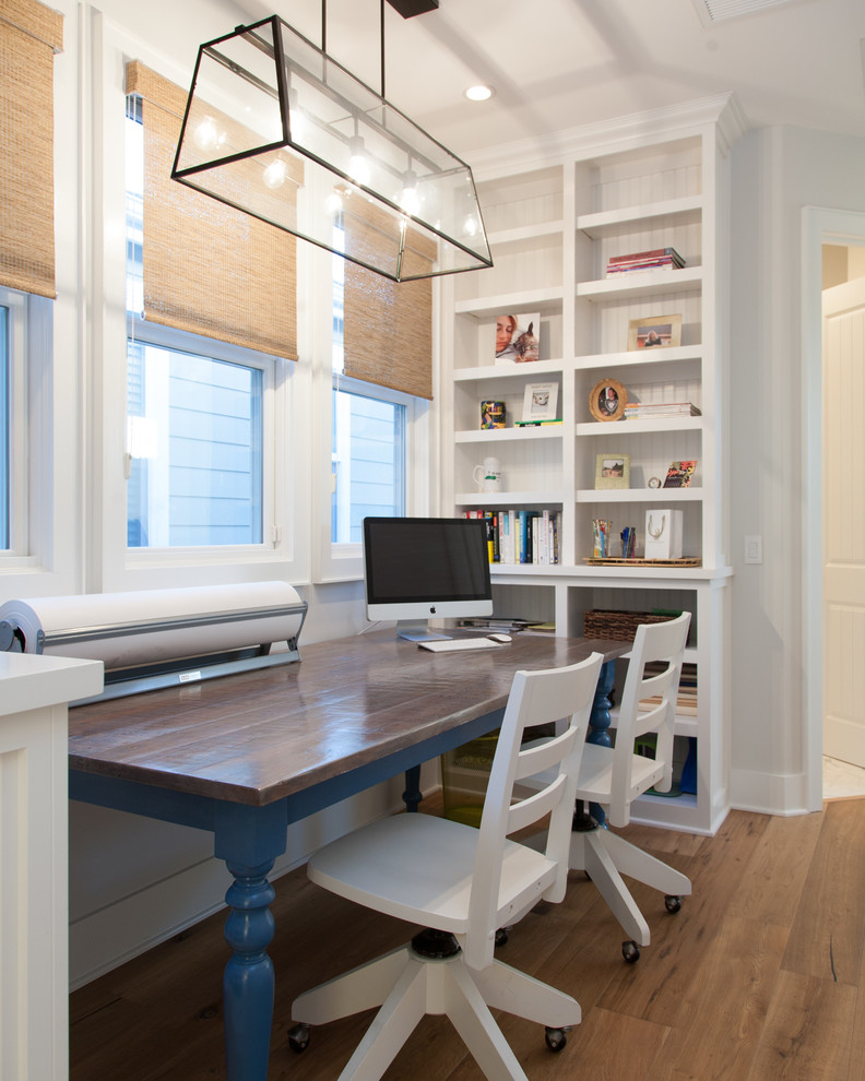 Beach style freestanding desk medium tone wood floor home office photo in Orange County with white walls